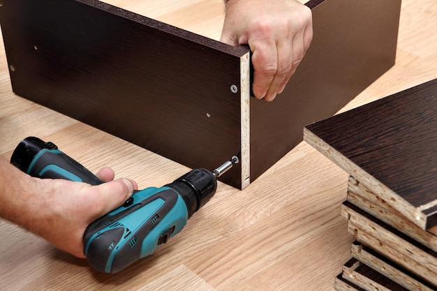 Assemblaggio di mobili da truciolare, utilizzando un cacciavite a batteria, da vicino.