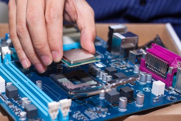 Assemblaggio di personal computer ad alte prestazioni, inserimento di cpu, processore nel socket della scheda madre, case del pc aperto sullo sfondo, profondità di campo ridotta, messa a fuoco a portata di mano