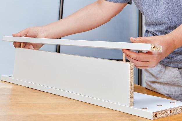 Assemblaggio di mobili, installatore che mette insieme due pannelli truciolari con accessori collegati al mobile come perno di legno.