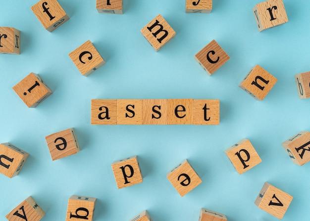 Parola di asset sul blocco di legno. vista piatta su sfondo blu.
