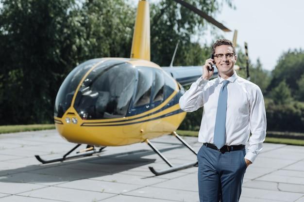 Assistenza necessaria. affascinante giovane amministratore delegato che chiama un militare di elicotteri e lo informa della necessità di lavori di riparazione