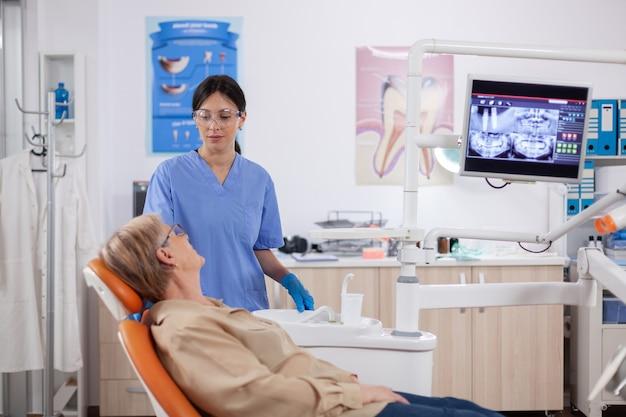 Assistente in clinica odontoiatrica che interroga il paziente anziano sui problemi ai denti