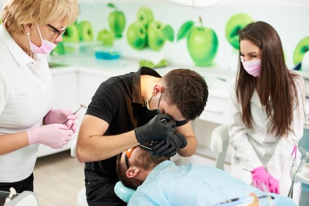 L'assistente dentista in presenza di un medico prepara il paziente a rimuovere il dente