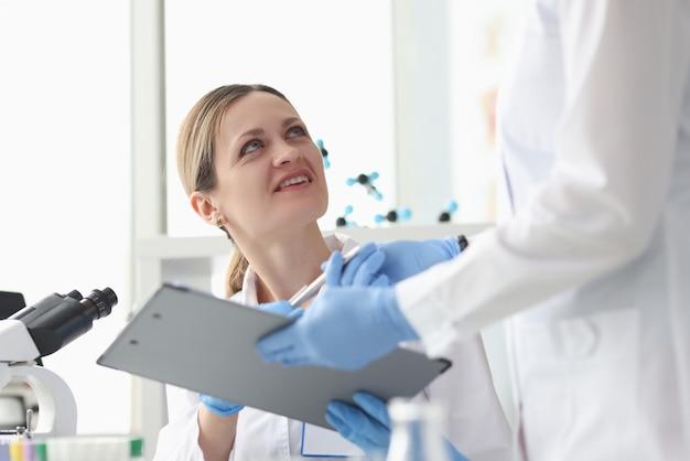 Assistente che dà la lavagna per appunti del chimico della donna con i documenti nel risultato del laboratorio della ricerca di chimica