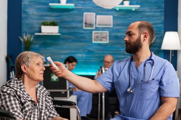 Assistente dell'uomo che controlla la temperatura utilizzando un termometro medico a infrarossi