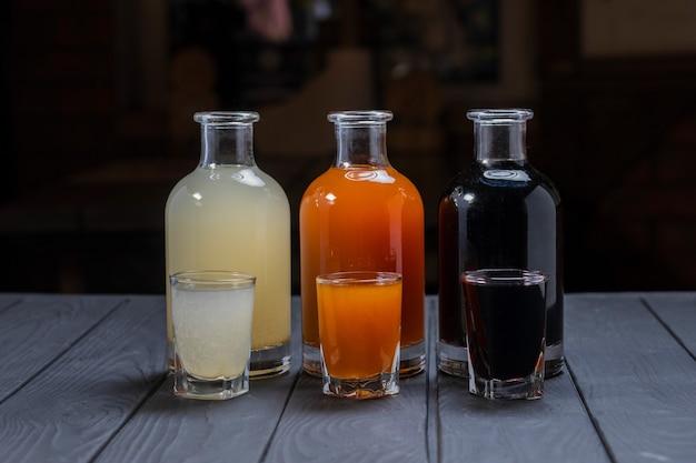 Sciroppi alcolici assortiti in bicchieri e caraffe su superficie di legno scuro