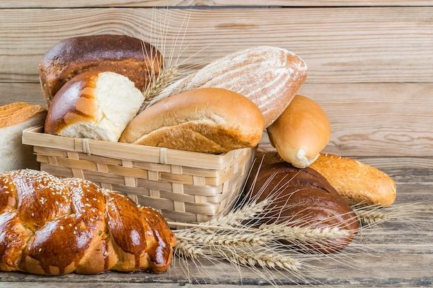 Pane assortito e spighe di grano sulla vecchia tavola di legno, sfondo di cibo