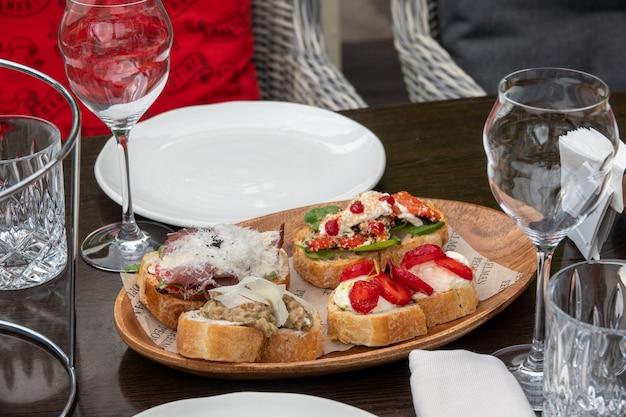 Bruschette assortite con vari condimenti. bruschette appetitose o crostini crudi. varietà di piccoli panini. bruschette miste