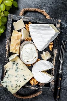Piatto di formaggi assortiti con brie, camembert, roquefort, parmigiano, crema di formaggio blu, uva e noci. sfondo nero. vista dall'alto.