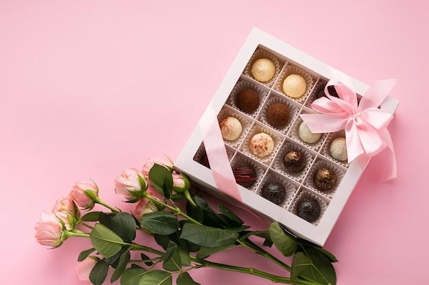 Cioccolatini assortiti in una scatola decorata con nastro di raso rosa, fiocco di fiori rosa freschi su rosa