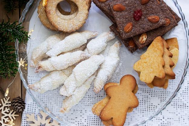 Biscotti assortiti, rami di abete e una ghirlanda su sfondo chiaro. stile rustico, messa a fuoco selettiva.