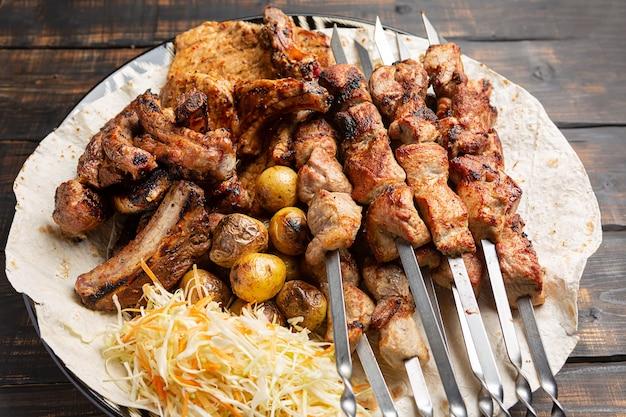 Deliziosa carne alla griglia assortita su spiedini con verdure fresche e patate al forno