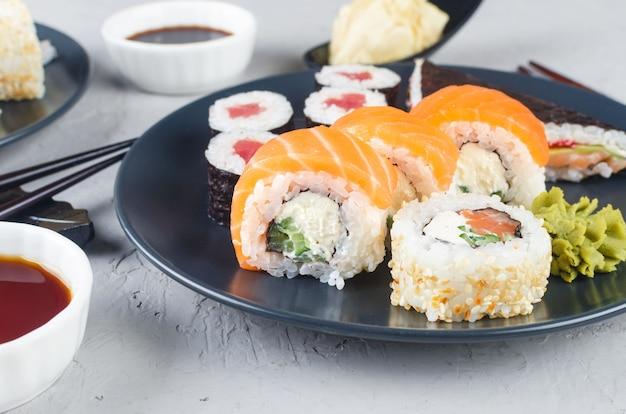 Rotoli di sushi diversi assortiti su un piatto e salsa di soia, zenzero, wasabi e bacchette Foto Premium