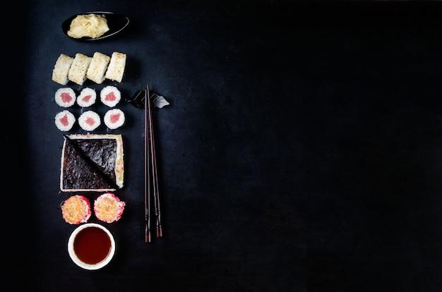 Rotoli di sushi diversi assortiti, salsa di soia, zenzero, wasabi e bacchette