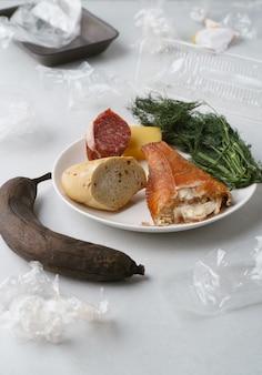 Rifiuti alimentari assortiti e involucro di plastica