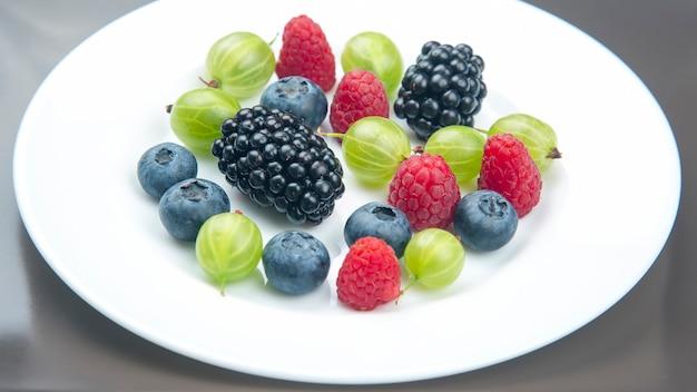 Frutti di bosco diversi freschi assortiti su un piatto bianco