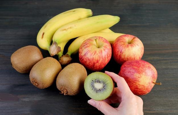 Frutta matura fresca assortita su fondo di legno nero con la mano che tiene un kiwi tagliato