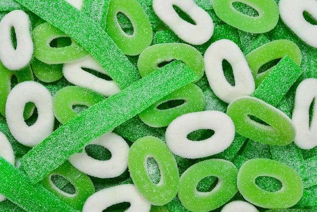 Sfondo di caramelle gommose verdi assortite. vista dall'alto. dolci di gelatina.
