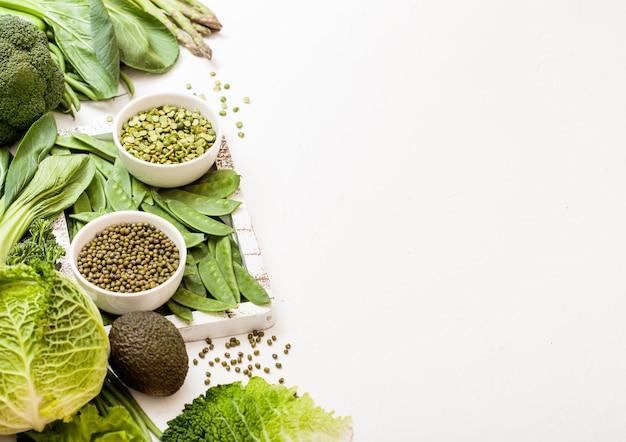 Verdure organiche crude tonica verde assortite su superficie bianca