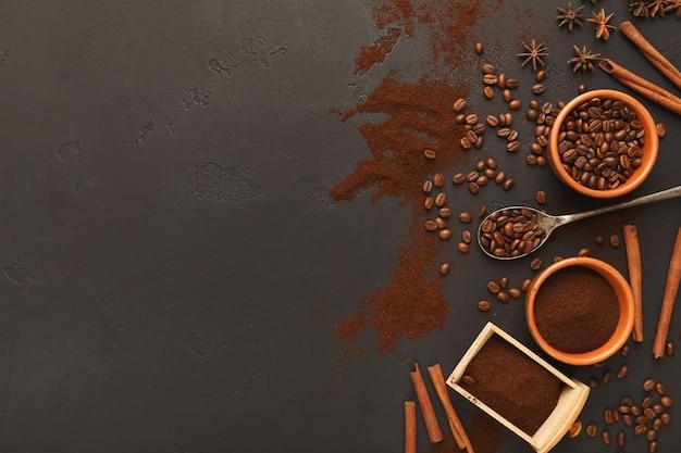 Caffè macinato assortito e fagioli tostati in ciotole e sparsi su ardesia grigia strutturata, vista dall'alto, spazio copia. modello di progettazione per pubblicità di bar o caffetteria