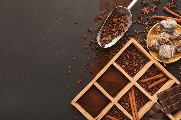 Caffè macinato assortito e chicchi tostati in cornice quadrata di legno e ciotole su ardesia testurizzata grigia, vista dall'alto, spazio copia. modello di progettazione per pubblicità di bar o caffetteria