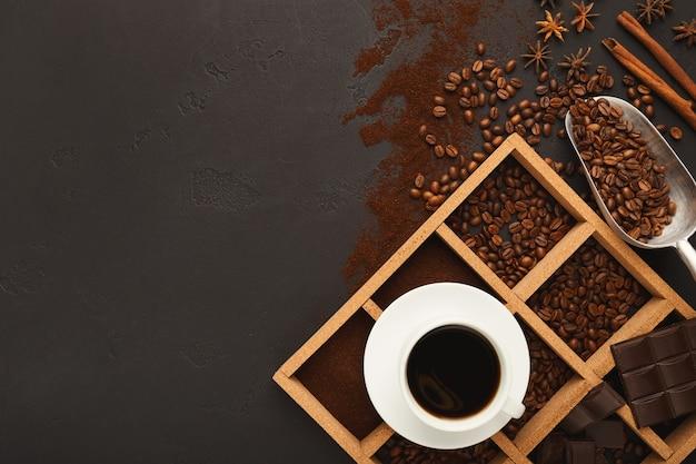 Caffè macinato assortito e chicchi tostati in cornice quadrata di legno su ardesia testurizzata grigia. vista dall'alto sulla tazza con bevanda e macinino vintage, copia spazio. modello per pubblicità di bar o caffetteria