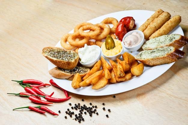 Snack caldi assortiti. formaggio arrosto, crostini, anelli di cipolla con ketchup