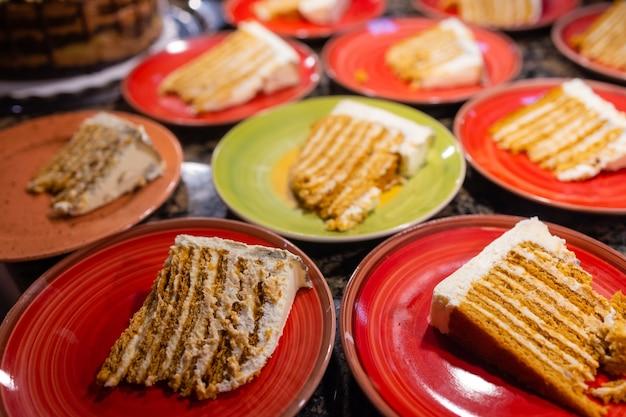 Grandi pezzi assortiti di torte diverse: cioccolato, lamponi, fragole, noci, mirtilli. pezzi di torta su un tavolo nero.