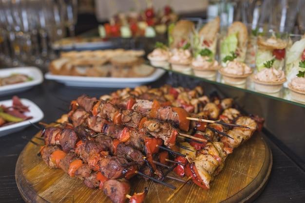 Carne assortita su un piatto da vicino. diversi tipi di carne e patate in un mucchio. antipasto su un piatto grande con salse.