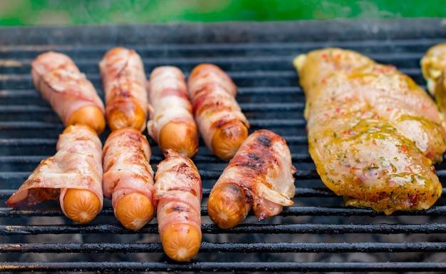 Grigliata mista assortita di carne di pollo e maiale, salsicce arrostite sulla griglia del barbecue cotte per la cena estiva in famiglia.