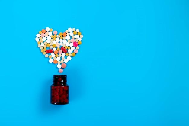 Pillole di medicina farmaceutica assortite, compresse per il trattamento delle malattie cardiache. a forma di cuore e una bottiglia di pillole.