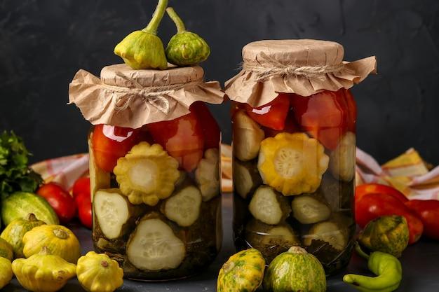 Cetrioli sottaceto assortiti, patissons e pomodori in barattoli su sfondo scuro, orientamento orizzontale, primo piano