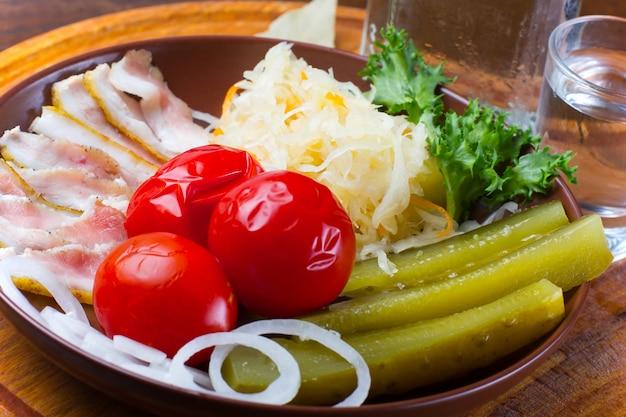 Sottaceti assortiti e verdure sottaceto con fette di pancetta