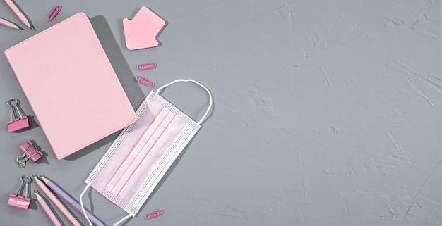 Forniture di cancelleria per ufficio e scuola rosa assortite su sfondo grigio con maschera medica, vista dall'alto, spazio copia