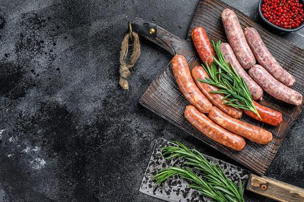 Salsicce chorizo crude assortite su un tagliere di legno. sfondo nero. vista dall'alto. copia spazio.