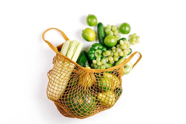 Verdure verdi biologiche fresche crude assortite in sacchetto di cotone ecologico. disposizione piatta, vista dall'alto