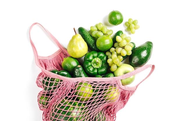 Verdure verdi biologiche fresche crude assortite in sacchetto di cotone ecologico rosa. disposizione piatta, vista dall'alto