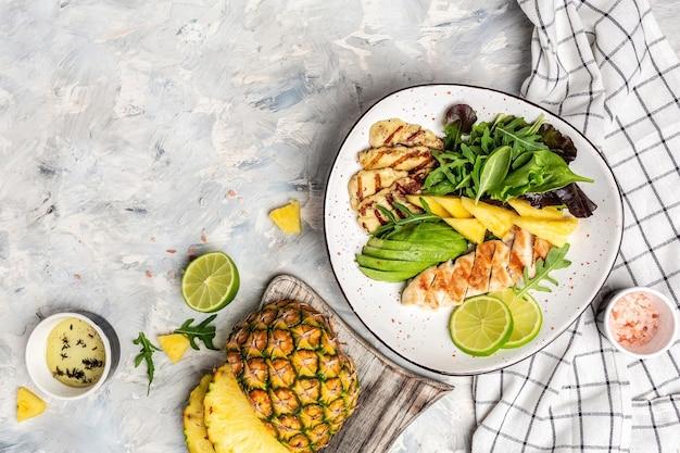 Pranzo in insalatiera assortita con pollo alla griglia, halloumi, avocado, rucola verde, lime