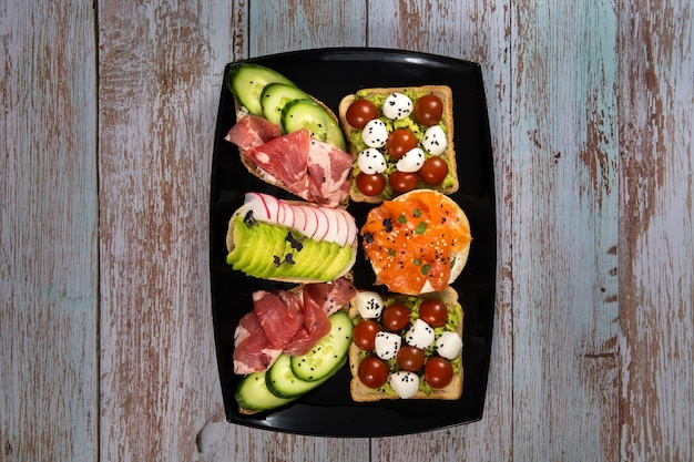 Panini assortiti con pesce, formaggio, carne e verdure su un piatto nero e una superficie di legno.