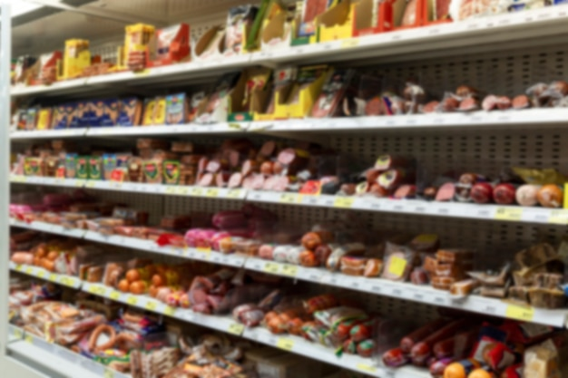 Salsicce assortite sugli scaffali del supermercato. sfocato.