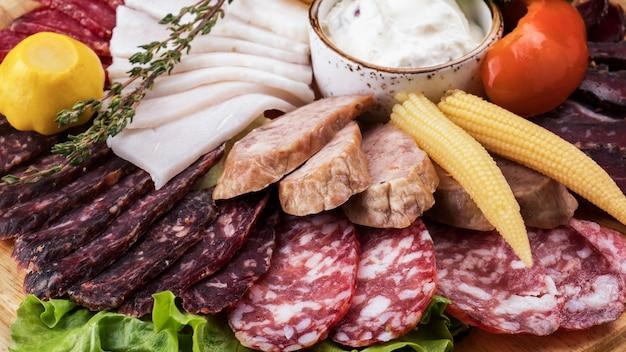 Assortimento di salsicce con verdure sottaceto su tavola di legno. avvicinamento