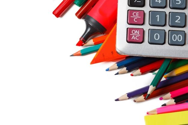 Materiale scolastico assortito, tra cui penne, matite, forbici, colla e un righello, su sfondo bianco