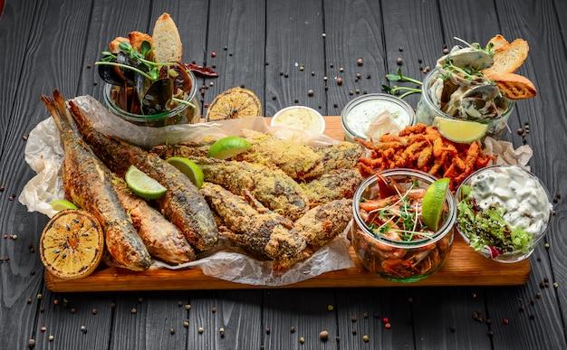 Antipasti di pesce assortiti, pesce fritto, cozze e gamberetti su una superficie di legno