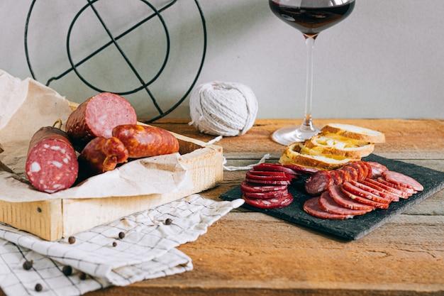 Salsiccie affumicate assortite, aperitivo a vino rosso su legno