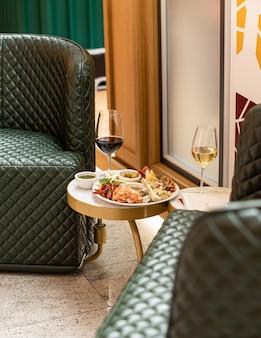 Snack assortiti. antipasto di formaggi, salumi, olive con due bicchieri di vino rosso e bianco in ristorante o bar.