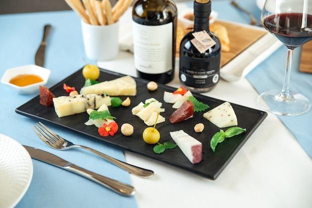 Piatto di formaggi spagnoli assortiti con vino rosso sul tavolo blu