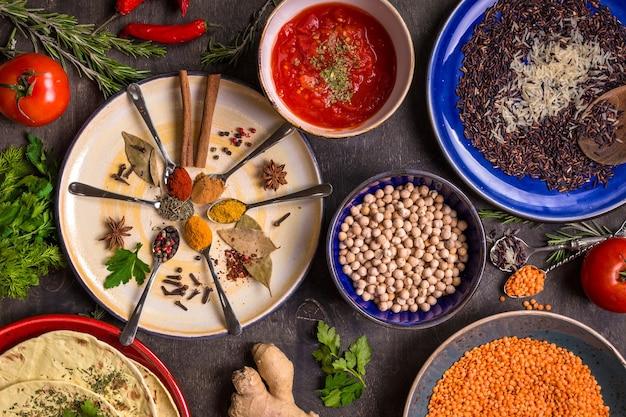 Spezie assortite, erbe aromatiche, ceci, lenticchie, basmati e mix di riso selvatico, chutney di pomodoro e pita su piatti colorati.