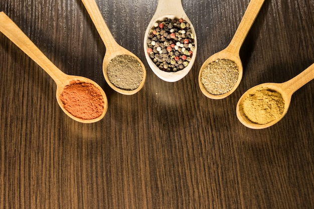 Spezie assortite in cucchiai di legno su un tavolo. vista dall'alto