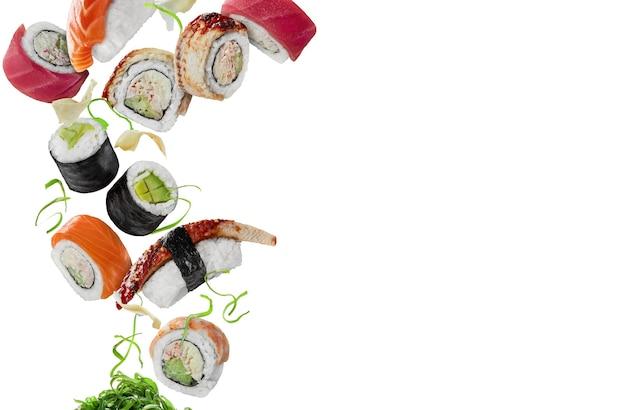 Sushi assortiti con zenzero sottaceto e wakame in bilico su sfondo bianco