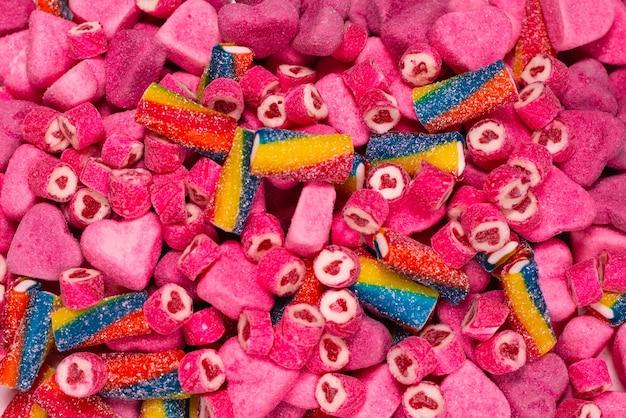 Caramelle gommose gustose assortite. vista dall'alto. sfondo di caramelle di gelatina rosa.